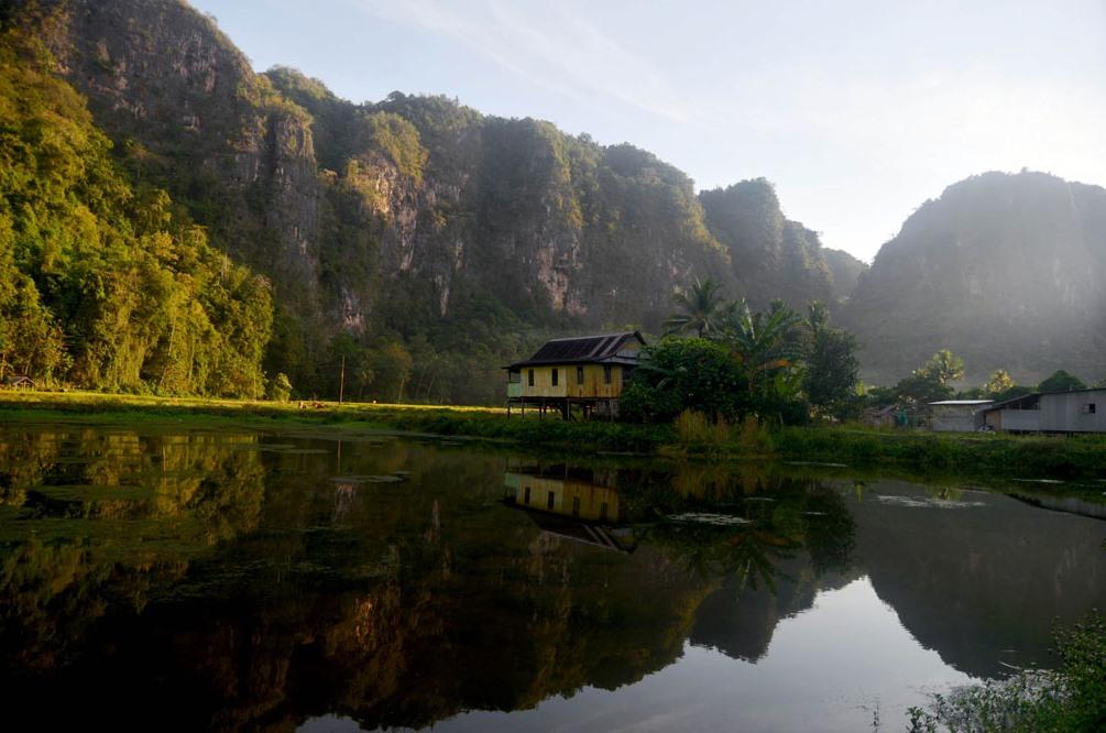 Refleksi rumah warga dengan Gugusan perbukitan karst saat pagi hari di Kampung Berua, Dusun Rammang-rammang, Maros, Sulawesi Selatan, Minggu 07 Agustus 2016. Menurut data badan lingkungan hidup Sulsel kawasan taman Karst Sulawesi Selatan kurang memiliki luas kurang lebih 43.700 hektar dan memiliki sekitar 280 goa, 16 diantaranya adalah situs goa prasejarah.TEMPO/Iqbal Lubis
